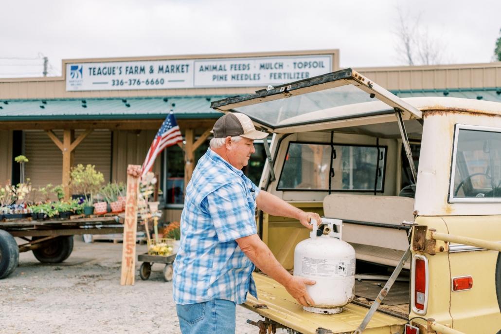 man putting propane tank into truck